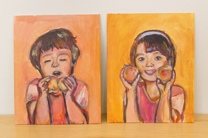 Two paintings of little girls smiling while holding peaches. The paintings are orange and pink in tone.