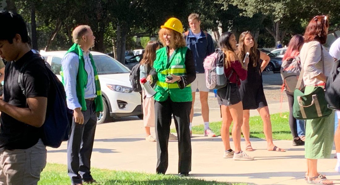 Emergency drill staff members, a man in a green vest and a woman, with a green vest, but also a hard hat — the man standing to the left of the woman — stand on grass in the midst of students outside due to an earthquake drill