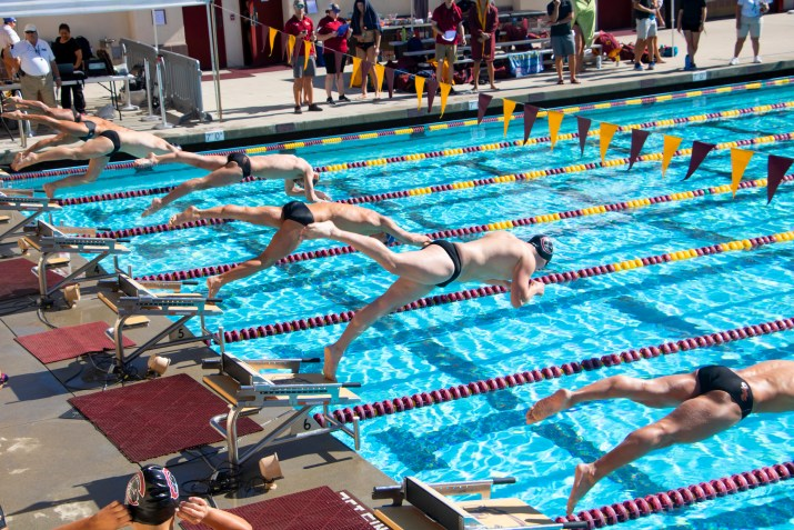 Multiple swimmers dive off platforms into a pool.