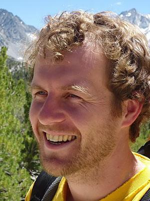 A man with blonde hair, in a yellow shirt and wearing a backpack, smiles to the side with mountains in the background.
