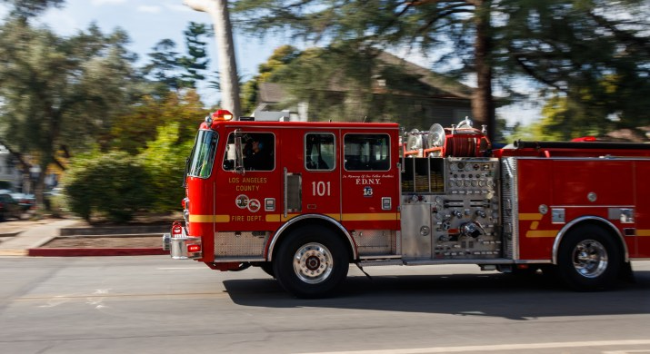 An emergency fire department vehicle rushes by on a residential street.