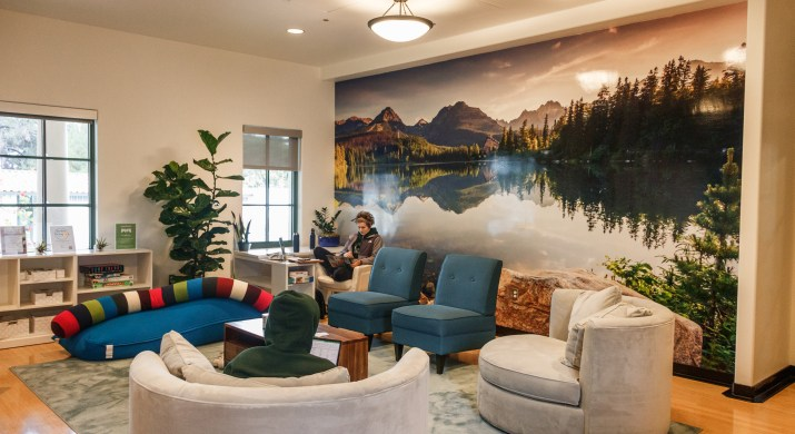 Students sit in a lounge area with a soft grey carpet and blue and grey comfy couches and chairs. The wall displays a floor-to-ceiling image of an alpine lake surrounded by pine trees and mountains.