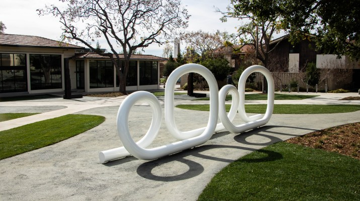 A white looping sculpture sits outside of a dining hall.