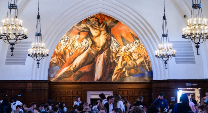 A colorful mural is on the wall above students who are eating.