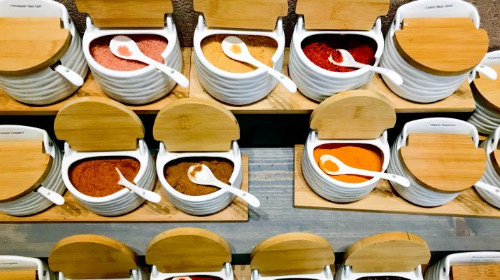Six open containers of spices with spoons sit on a shelf.