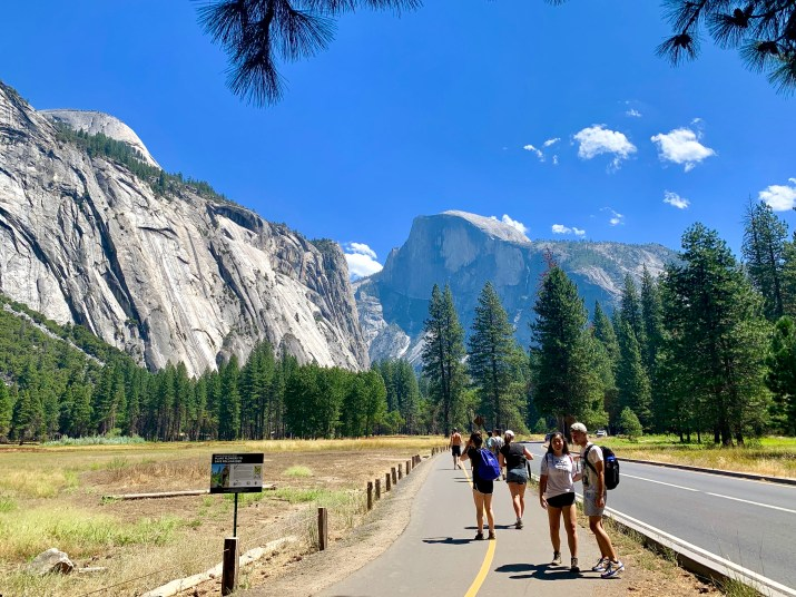 The mountains and trees of Yosemite fill the frame, while a trail of students to the right of the image walk away from the camera.