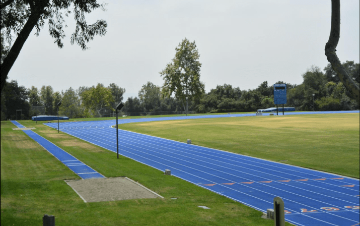 Pomona's blue Strehle running track is surrounded by grass and trees.