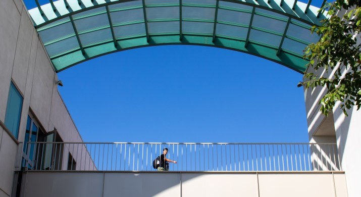 A student walks across a bridge between two buildings underneath an archway.