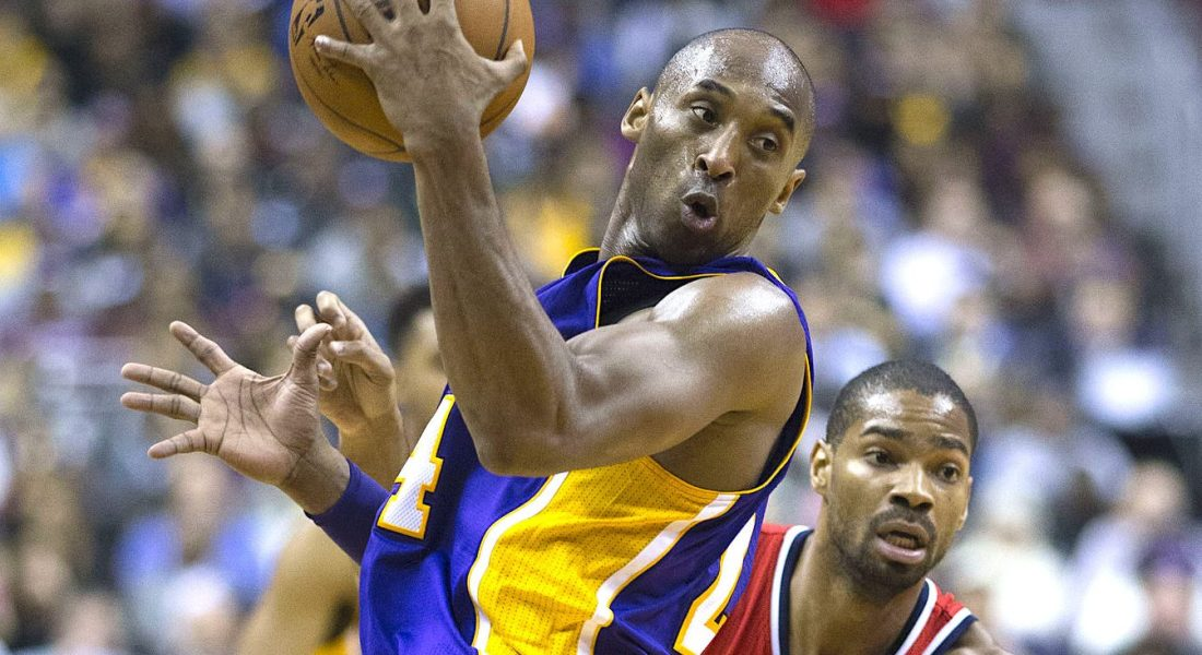 A man wearing a basketball jersey and holding a basketball twists pass a second man who is attempting to defend him.