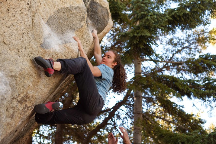 A woman in the center of the image scrambles up a rock face, holding on precariously to ridges and divots. A pair of hands at the very bottom of the image are extended, ready to catch the climber if she falls. There are evergreen trees in the background.