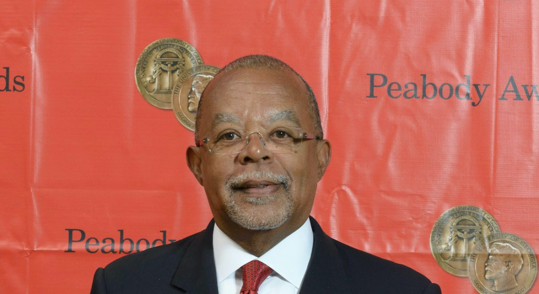 An African American man with glasses in front of a red backdrop