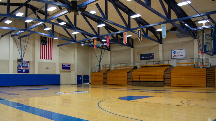 An empty basketball court fills the screen, with the bleachers rolled up and various signs posted on the walls.