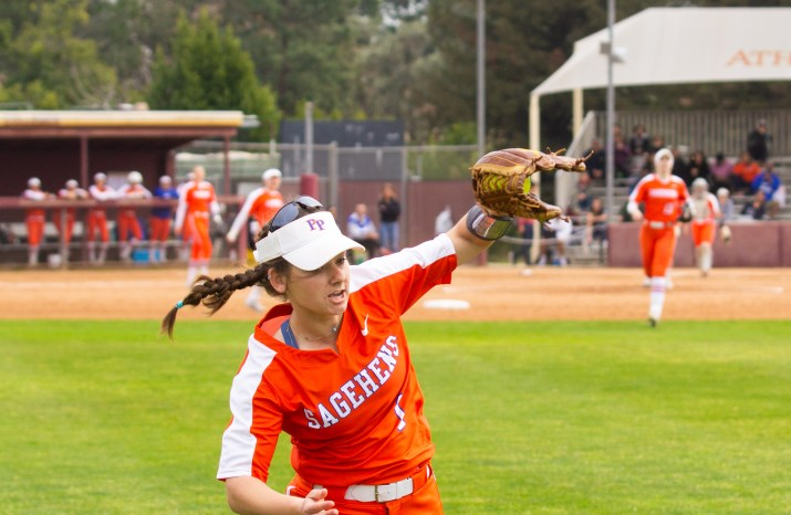 A woman runs toward the camera while catching a softball as other softball players watch from the field and dugout.