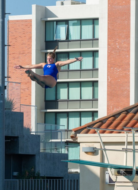 A woman is suspended in the air after jumping off a diving board, with her legs pointed straight in front of her and her arms pointed out to the side. A diving board is below her and there is a large building in the background.