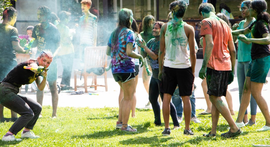 Many students covered in colorful handprints stand in a circle with another student pointing at the camera.