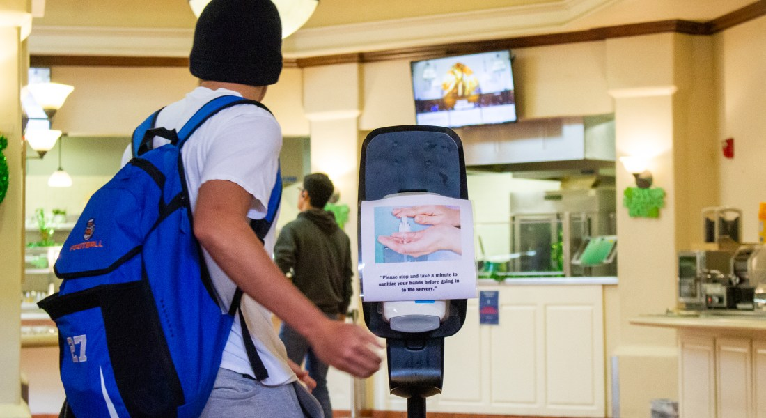 """A sign that says """"please stop and take a minute to sanitize your hands before going into the servery"""" on the front of a hand sanitizer dispenser."""