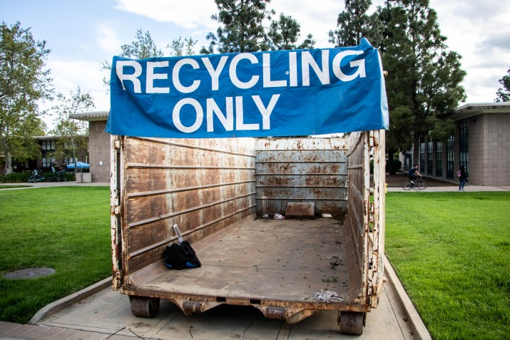 "A dumpster with a sign reading ""Recycling Only"" sits on the lawn."