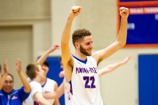A male basketball player stands with his fists raised and smiles as his teammates celebrate behind him.