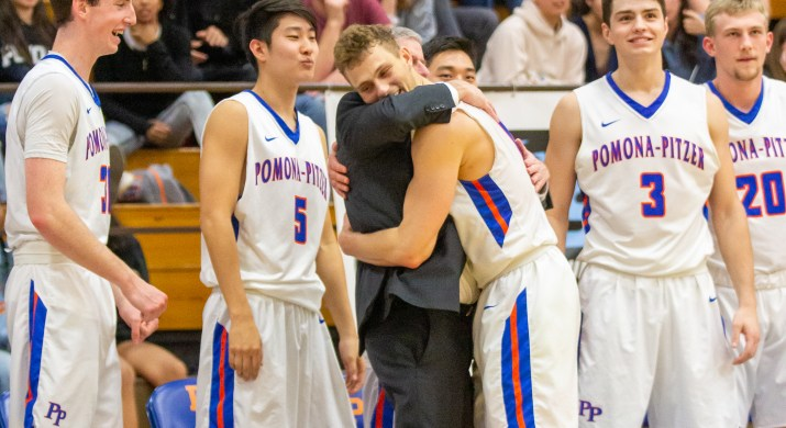 A male basketball player hugs a coach wearing a suit in the center of the image. Behind them are other smiling basketball players and a crowd paying rapt attention to the game.