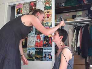 a smiling girl shaves the head of another smiling girl in a dorm room