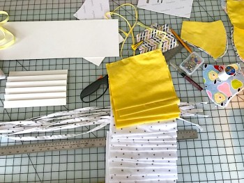 Yellow and and white fabric on a table, ready to be made into masks.
