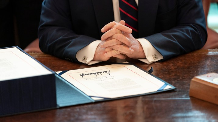 a white man's folded hands at a wooden desk in front of a piece of paper with signature in sharpie