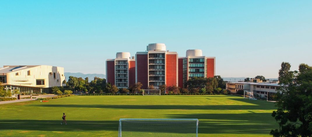 A green athletic field with a goal is in front of tall, orange, buildings.
