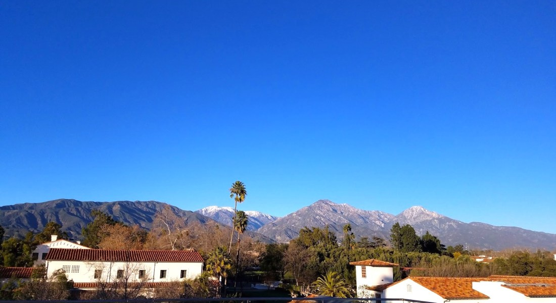 A view of the blue sky and mountains, with some Scripps College buildings in the foreground.