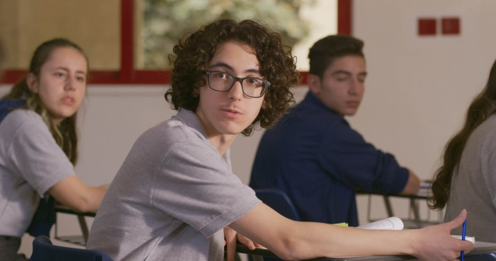 A boy with a glasses and curly hair looks off into the distance.