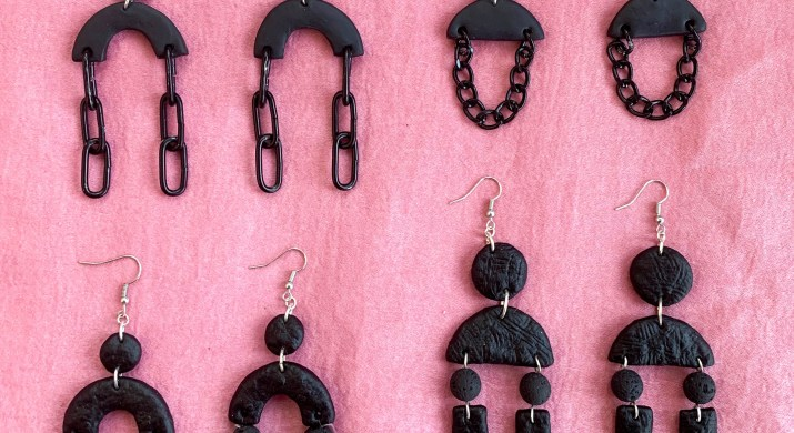 Four pairs of black earrings sit on a pink background.