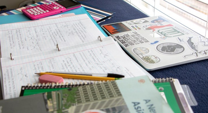 A laptop, binder, pencils, and books sit on a blue desk.