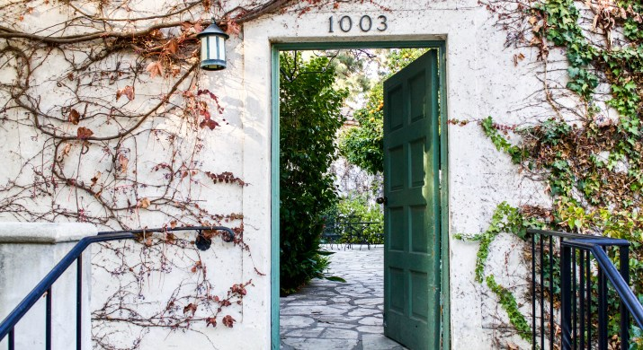 A photo of an ajar green door in a stucco cream wall covered in ivy. Above the door is an address: [1003].