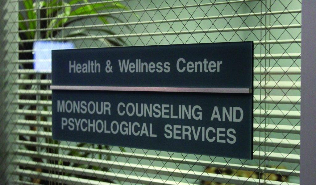 "A nameplate on a window reads ""Health and Wellness Center"" and another below reads ""Monsour Counseling and Psychological Services."""