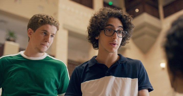 Two boys, one with a green shirt and the other with a blue shirt and glasses, look off camera.