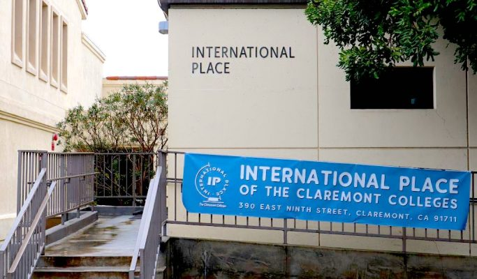 """A tan-colored building displays a blue banner that reads """"International Place of the Claremont Colleges."""""""