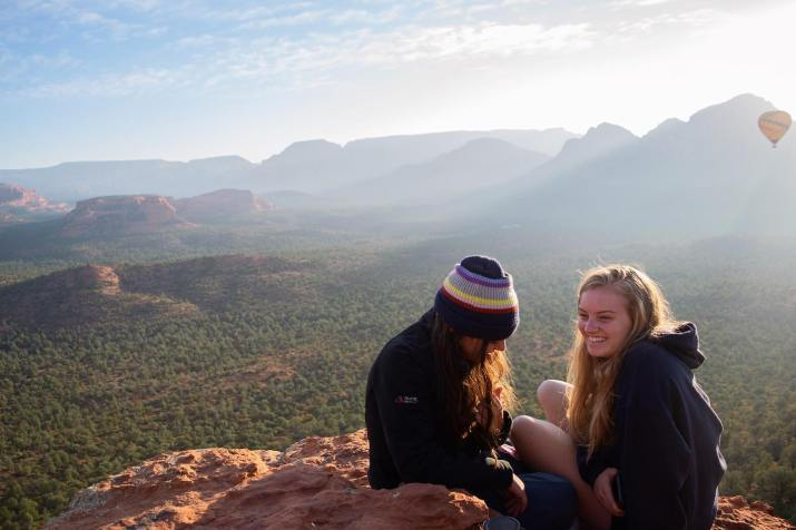 Two female college students sit atop a mountain overlooking a forest.