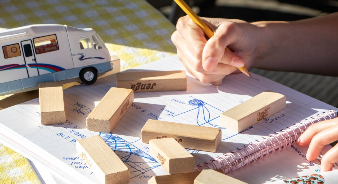 A person writes on a paper covered in children's toy blocks.