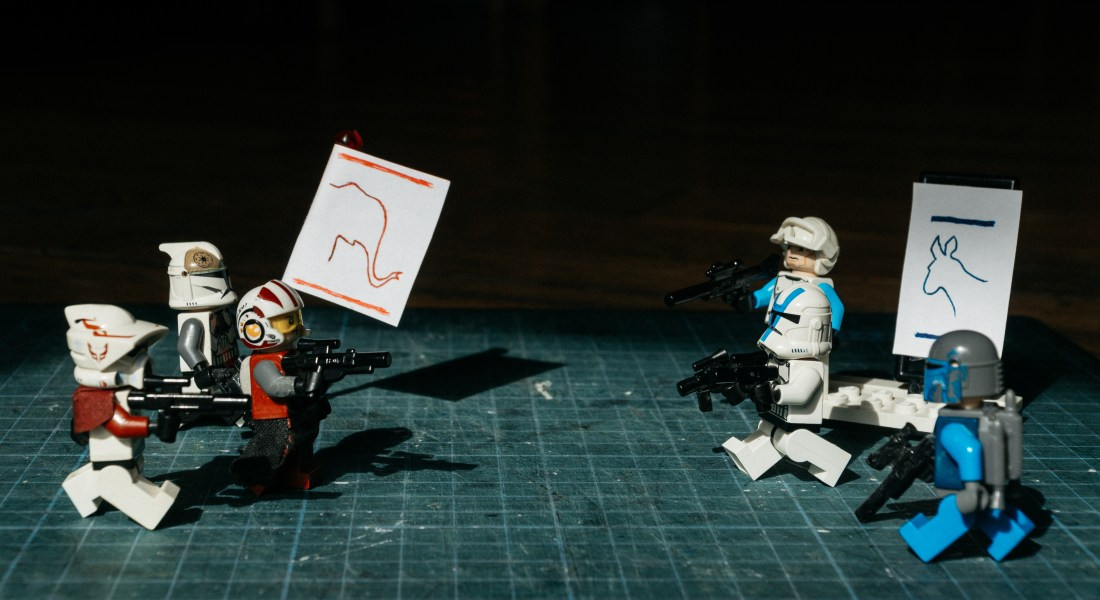 A group of red Lego figures holds up a sign with an elephant, while a blue Lego group holds up a donkey sign. The characters shoot at each other.