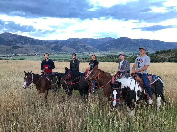 Five male college students pose for a photo while riding horses through a field. In the background there is a mountain range.