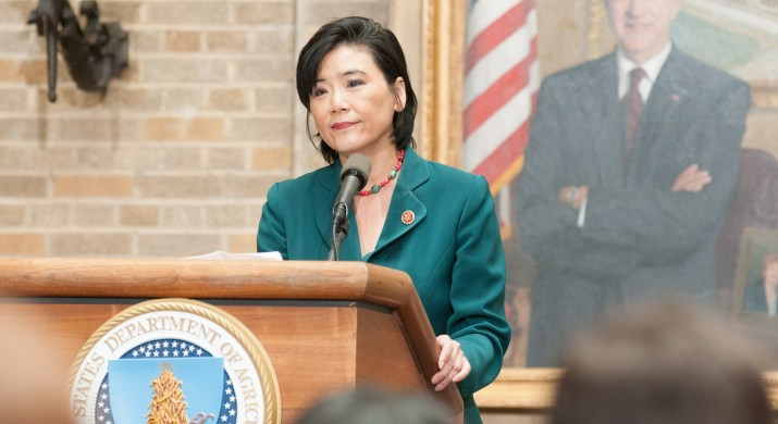 A woman wearing a blue suit stands at a podium.