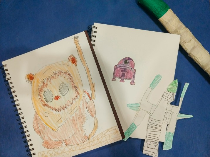 Notebooks are open to childrens' drawings of Baby Yoda, R2D2, an Ewok, and a lightsaber.