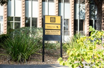A Harvey Mudd College sign with directions to buildings sits in a quad.