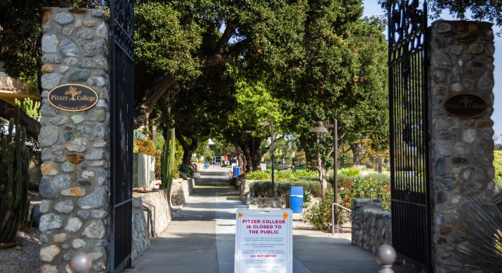 """A cement pathway is bordered by wrought iron gates and stone pillars. A sign along the path reads """"Pitzer College is closed to the public. Do not enter."""""""
