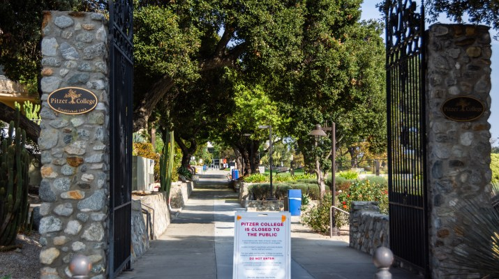 "A cement pathway is bordered by wrought iron gates and stone pillars. A sign along the path reads ""Pitzer College is closed to the public. Do not enter."""