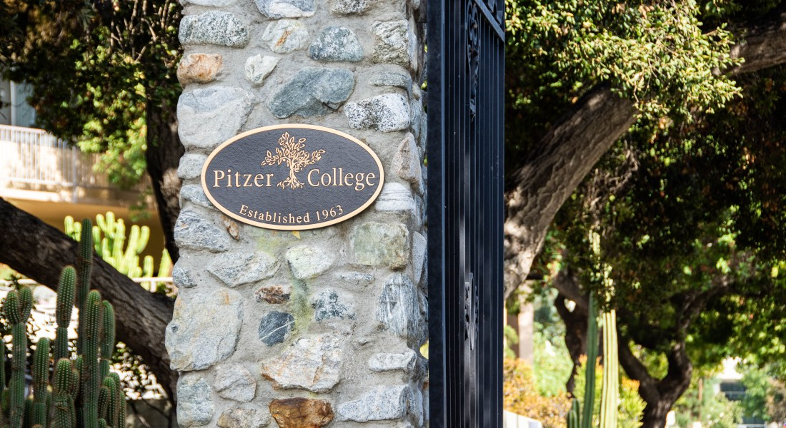 "A sign reading ""Pitzer College Established 1963"" is on a stone gate."