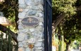 """A sign reading """"Pitzer College Established 1963"""" is on a stone gate."""