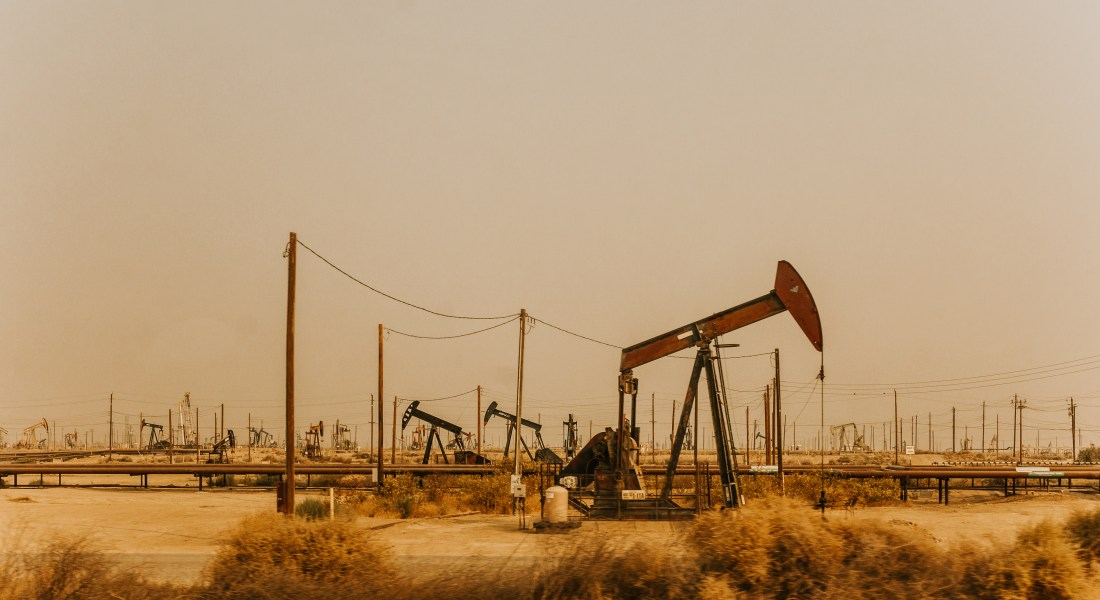 Dozens of oil pumps dot a desolate field along the side of a highway.
