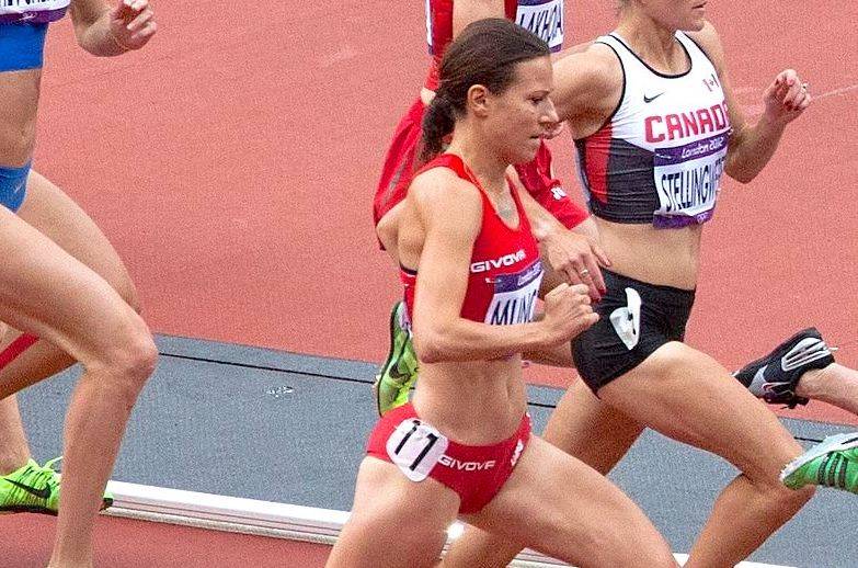 A woman in red along with many other women run on a track.