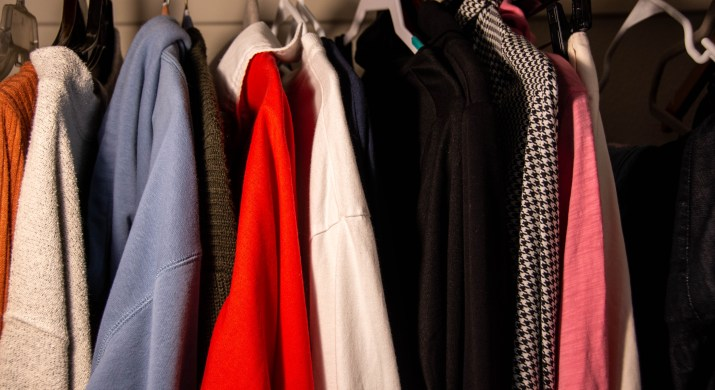 Multiple shirts hang in a closet.