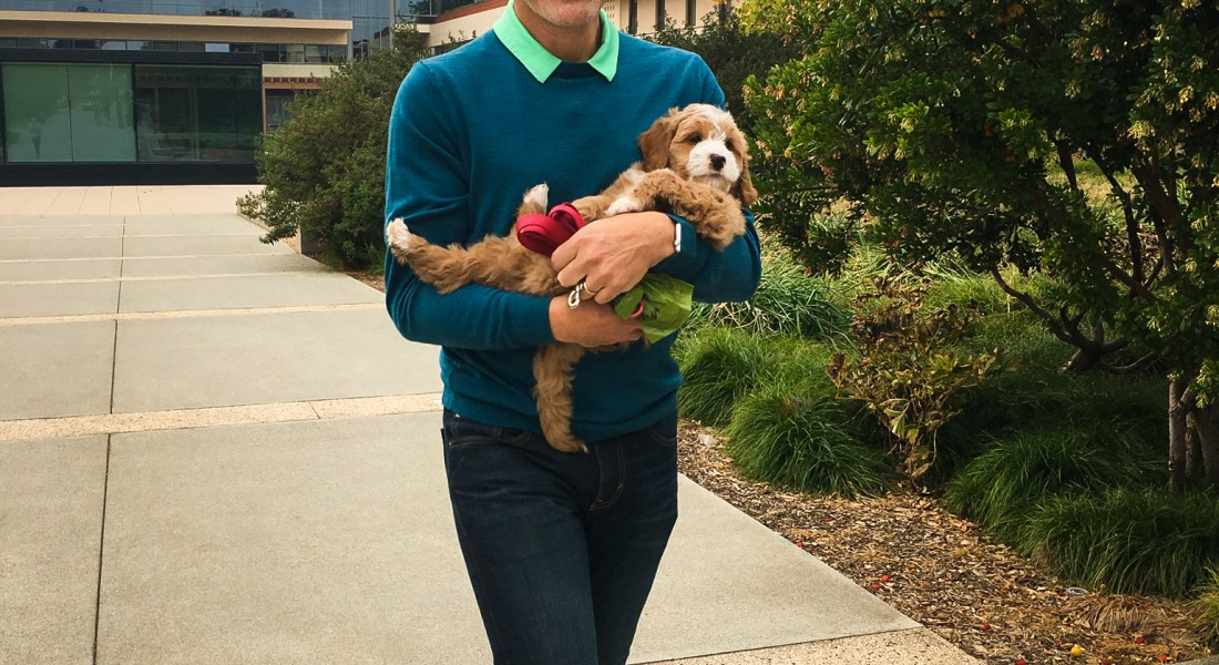 A man walks while holding a small, yellow dog.